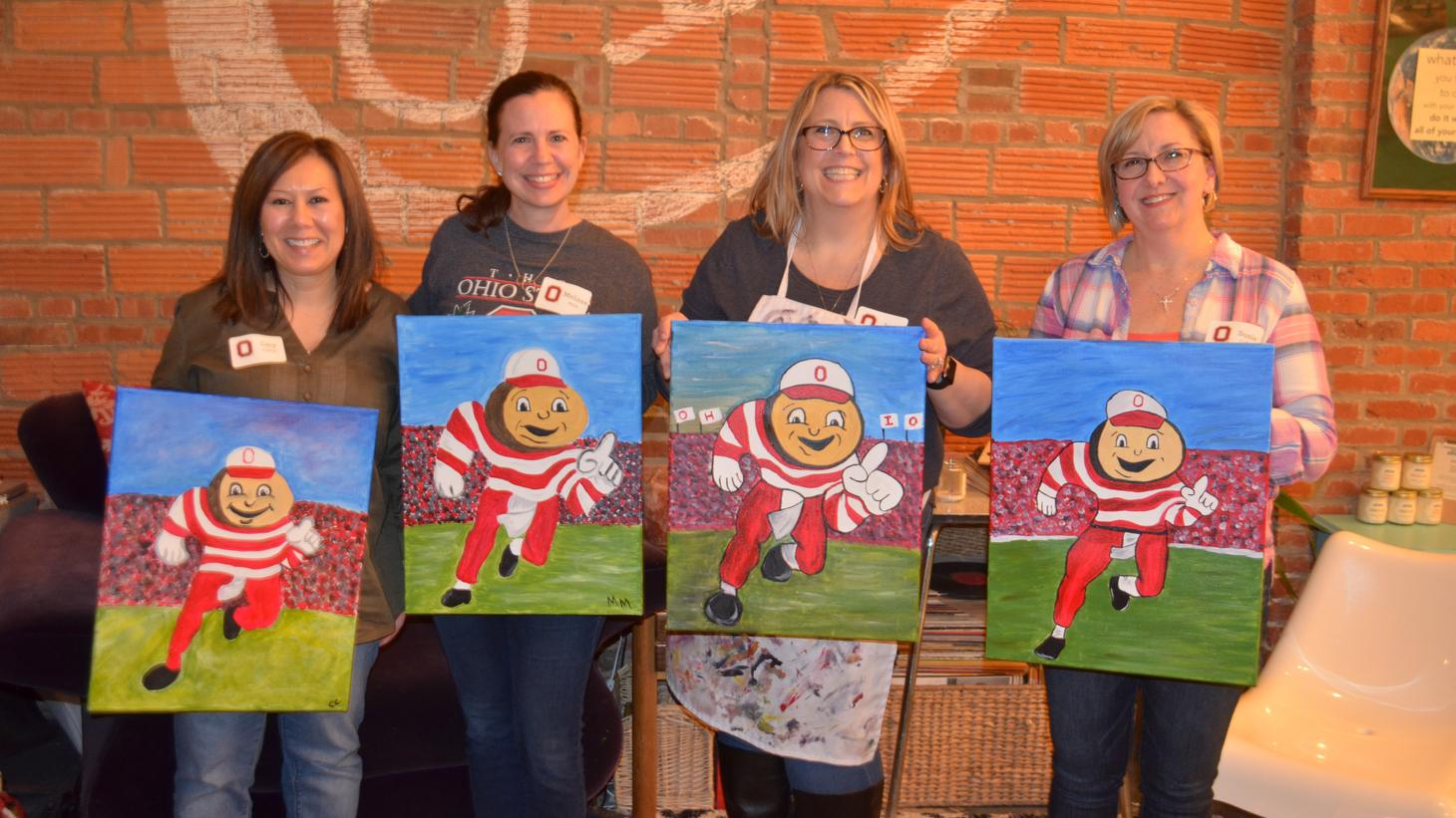 group of alumni pose with their paintings at a paint and pour event