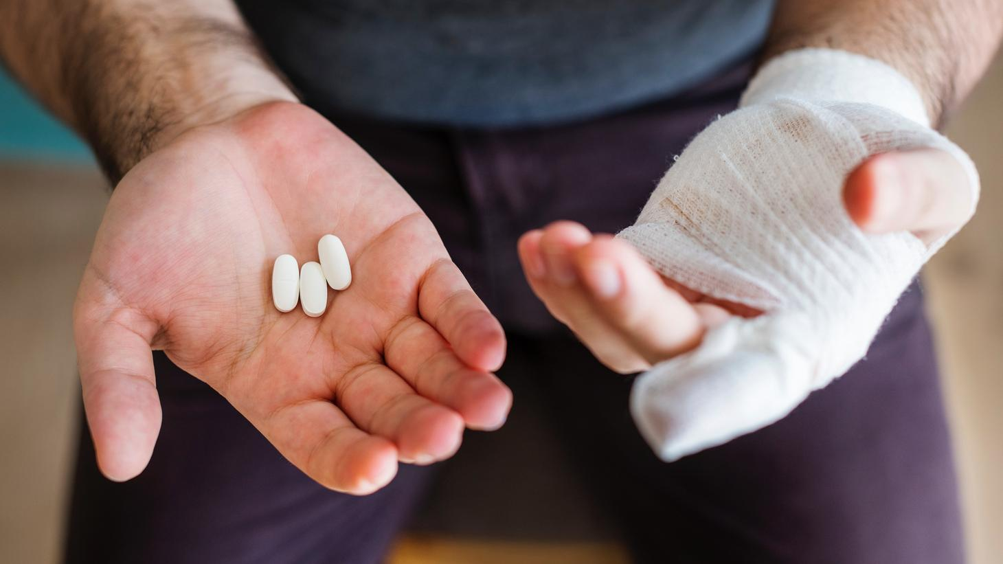 Close-up of two hands, one with a bandage and the other with 3 pills