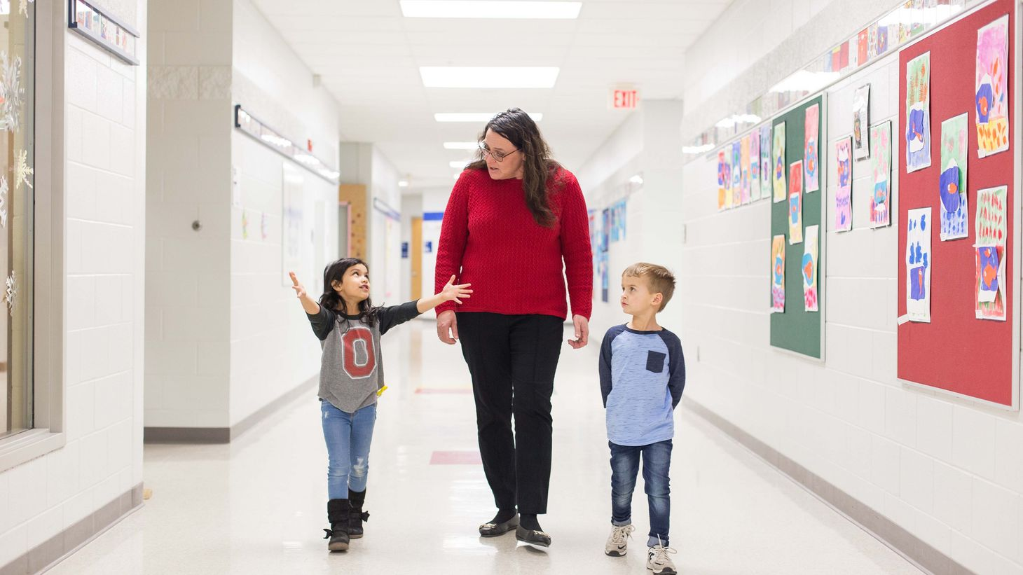 school nurse walking down hallway with two young students
