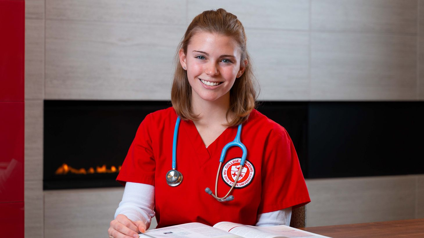 nursing student in red scrubs reading textbook