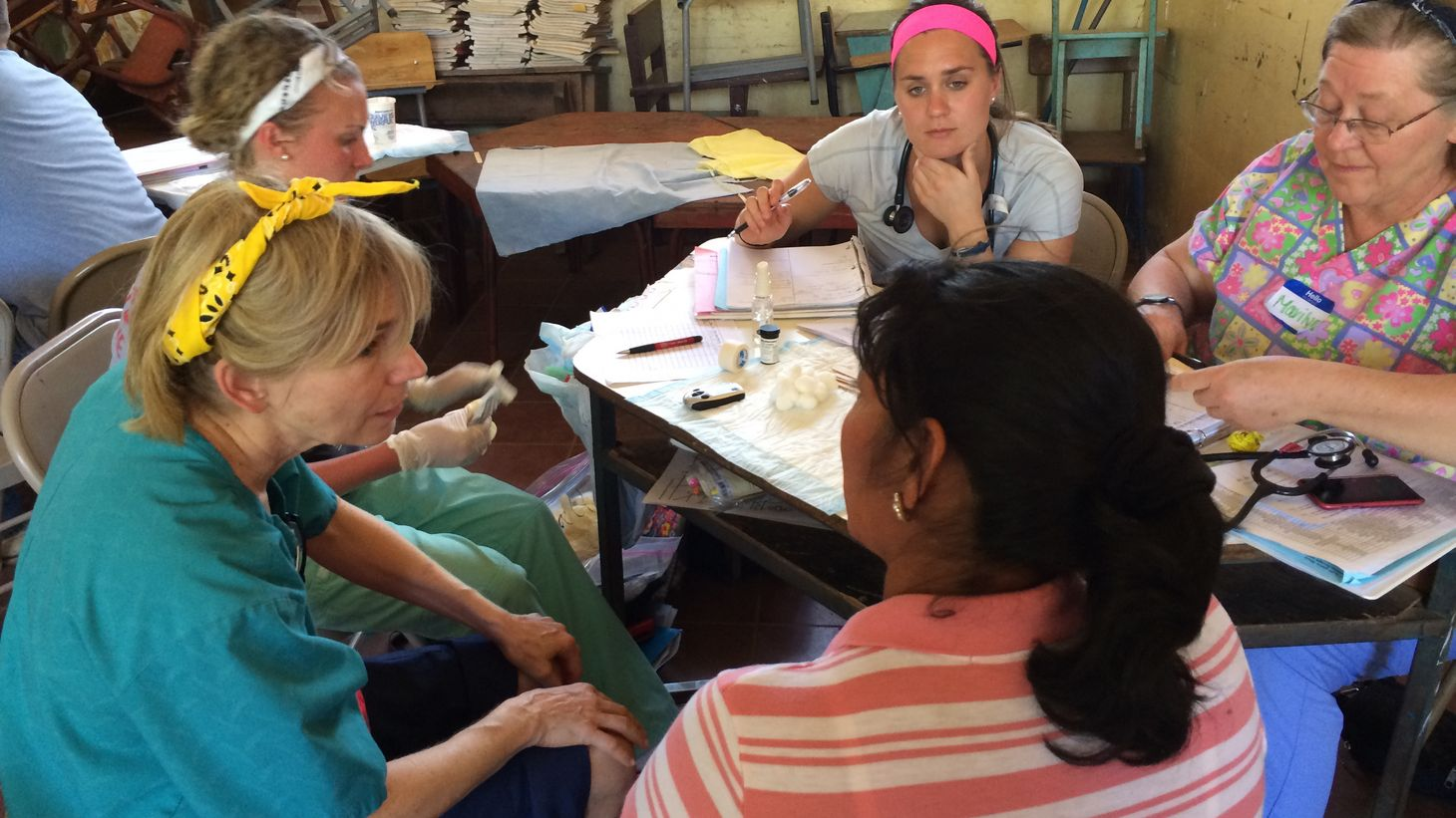 College of Nursing faculty and students in Honduras talking around a table