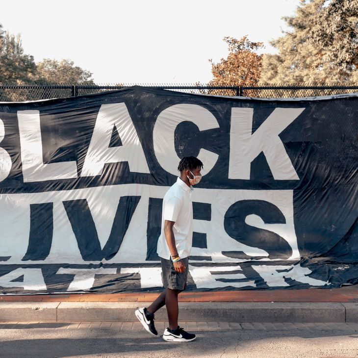man wearing a mask walking in front of a Black Lives Matter banner